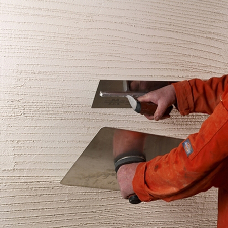 Image of render being applied to a wall with two trowels